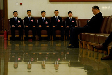 Security personnel sit at their position during the sixth plenary session of the National People's Congress (NPC) at the Great Hall of the People in Beijing