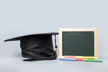 chalkboard, chalk with graduation cap on clean background.