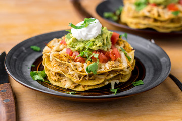 Crunchy chicken tostada stack. Tostadas are a type mexican food, made with crispy fried corn tortillas covered with layers of various ingredients such as chicken, guacamole, cheese, sour cream & salsa