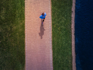 Active woman running jogging exercising in park aerial view