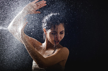 young girl portrait and splashing water in her face. beautiful female model on black background.
