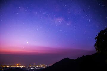 Milky way above city, twilight scene, Chiangmai, Thailand