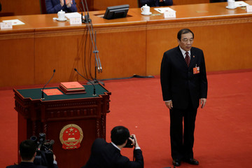 Newly elected head of the National Supervision Commission Yang Xiaodu stands after he takes the oath to the Constitution at the sixth plenary session of the NPC at the Great Hall of the People in Beijing