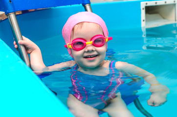 A little girl of European appearance in a pink rubber cap learning to swim in the pool in glasses for swimming