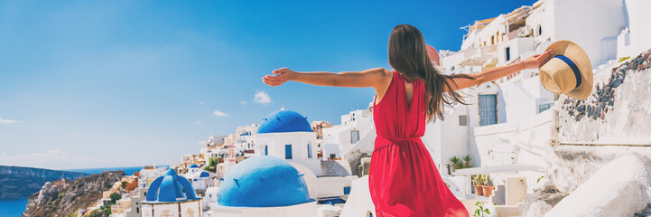 Wall Mural - Europe travel vacation fun summer woman feeling free dancing with arms open in freedom at Oia, Santorini, Greece island. Carefree girl tourist banner panorama.