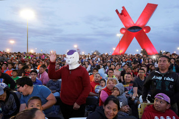 A man wearing a mask and other fans watch the episode 130 of the Dragon Ball Z anime at the Plaza de la Mexicanidad square in Ciudad Juarez