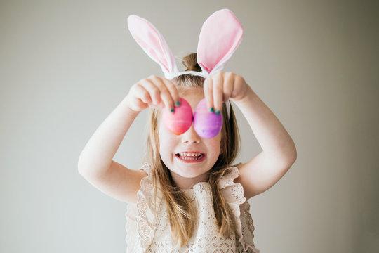 Little Girl Holding Easter Eggs in front of eyes
