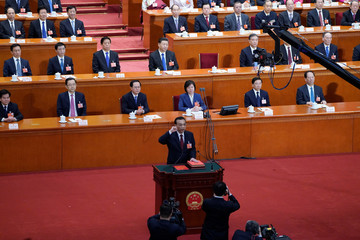 Chinese Premier Li Keqiang with his hand on the Constitution takes the oath, after he is voted as the premier for another term, at the sixth plenary session of the NPC at the Great Hall of the People in Beijing