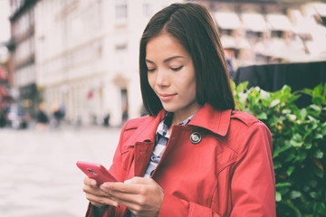 Phone Asian business woman texting sms on cellphone app in city street, urban lifestyle. Europe travel vacation tourist using smartphone outside. Chinese businesswoman in red trench coat.