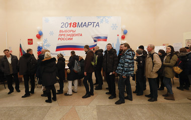 Russian citizens queue to cast their votes at a polling station during the presidential election in Baikonur