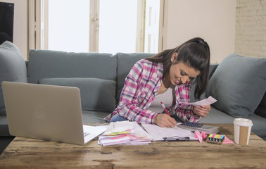 young attractive and happy hispanic woman checking bills bank papers expenses and monthly payments smiling at apartment living room