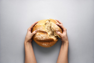 Fresh and hot / Creative concept photo of hands holding bread on grey background.