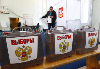 A man walks out of a voting booth at a polling station during the presidential election outside Moscow