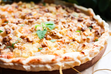 Homemade puff pastry pie or pizza with camembert cheese, conference pears, walnuts and fresh mint, selective focus. Picnic and snack food. Breakfast food. Summer food. Idea for snack pizza pie.