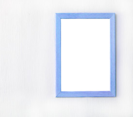 Wooden frame with blank sheet of paper on light wall. Copy space. Mock up concept