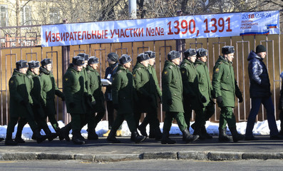 Servicemen walk outside a polling station during the presidential election in Moscow