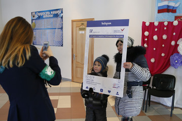 A woman and a child pose for a picture as they visit a polling station during the presidential election in Elektrogorsk
