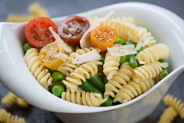 Closeup of fusilli pasta with vegetables and parmesan cheese, selective focus, shallow depth of field