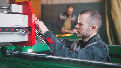 Portrait of electrician on overalls is working with energy panel and machinery equipment on plant