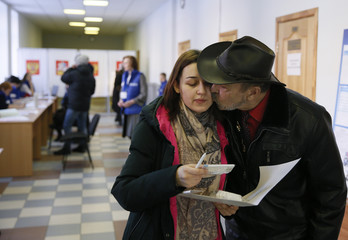 Student Vladislava Isaikina and her grandfather visit a polling station to cast their votes during the presidential election in Elektrogorsk