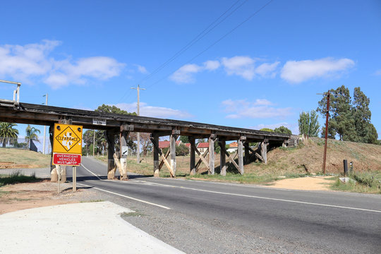 a yellow and black Low Clearance, Overheight Vehicles Must Stop sign at a low timber trestle bridge