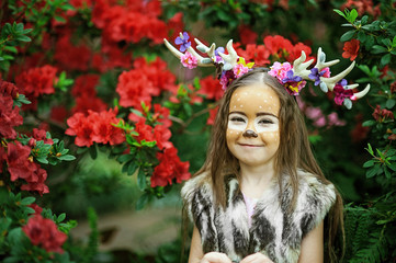Fairy tale girl. Portrait a little girl in a deer dress with a painted face in the forest. Big brown antler