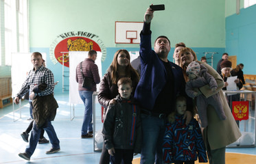 People take a selfie as they visit a polling station during the presidential election in Stavropol