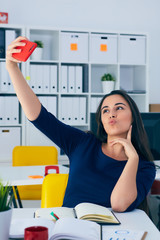 Portrait of a smiling woman making selfie photo on smartphone at the office background