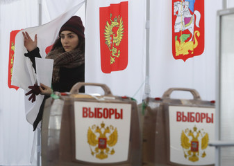 A voter walks out of a voting booth at a polling station during the presidential election outside Moscow