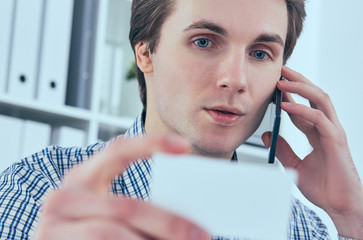 Close-up portrait of handsome european businessman talking on the phone and holding business card at workplace.