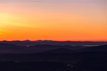 Beautiful aerial view of Umbria (Italy) valley at dusk, with hills, city lights and Trasimeno lake reflecting orange sky light