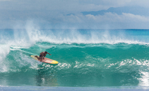 Surfer riding longboard on big green wave at Balangan beach, Bali, Indonesia