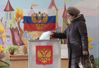 A voter casts her vote at a polling station during the presidential election in St. Petersburg