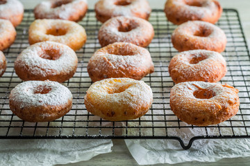 Homemade donuts with powdered sugar on metal grate