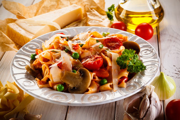 Pasta with vegetables on wooden background