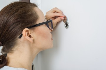 Woman looks through the peephole of the front door in the apartment Wall mural