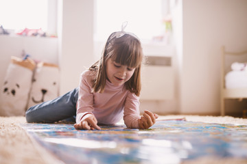 Beautiful charming little toddler girl lying on the carpet of her room and playing with a big map.
