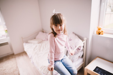 Charming cute little toddler girl sitting on the edge of the bed in her children room.