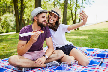 Loving young couple eating and taking selfie while on picnic in the park