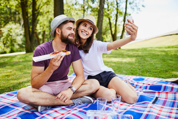 Young couple taking selfie while sitting and eating on picnic in the park