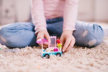 Close up focus view of a plastic toy car with umbrella and pink window on the carpet while little girl playing with them.