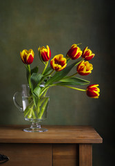 Still life with colorful tulips in the glass jug
