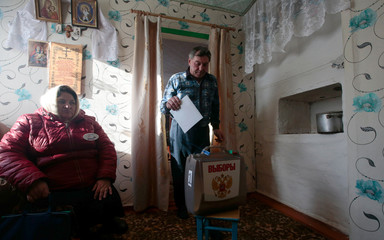 A local resident approaches a mobile ballot box as a member of an election commission sits nearby during the presidential election in Smolensk Region