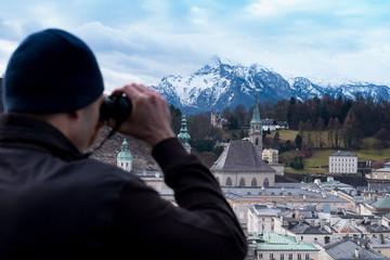 Man is watching Salzburg with binoculars from above. Austria, Salzburg city, Europe.