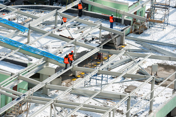 Construction site with workers on the building roof