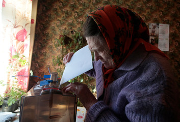 A local resident casts her vote into a mobile ballot box during the presidential election in Smolensk Region