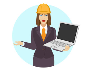 Businesswoman in construction helmet holding a laptop notebook and gesturing
