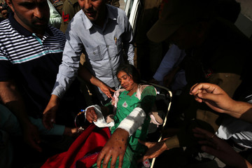 People shift a woman, who according to local media was injured in what they say was a ceasefire violation by the Pakistani troops along the Line of Control in Poonch district, towards a government hospital in Jammu