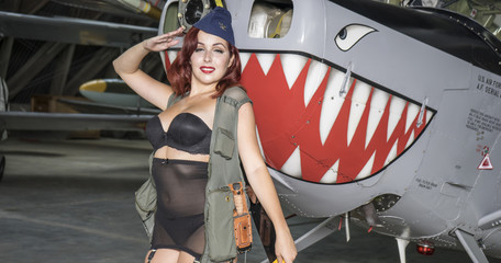 redhead woman dressed as a soldier next to a plane of the second world war, American pinup in the style of the 40s. sensual and sexy woman