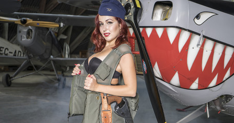 Bomber, redhead woman dressed as a soldier next to a plane of the second world war, American pinup in the style of the 40s. sensual and sexy woman